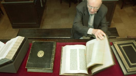 In a 2002 file photo, William H. Scheide opens one of the first four editions of the Bible ever printed, which he has loaned to the Scheide Library at the Firestone Library at Princeton University in Princeton, N.J.