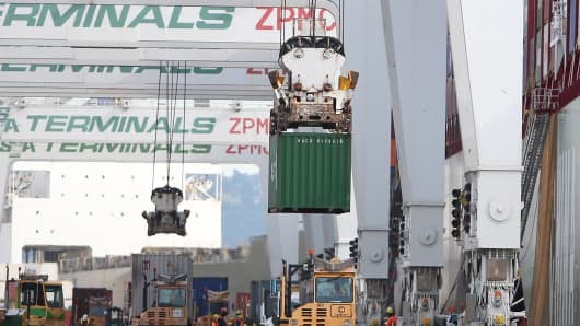 A container is loaded onto a ship docked at the Port of Oakland.