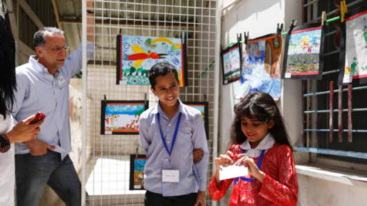 "Fadi Ghandour listens to two children on the ""dream path"" at Ruwwad. As part of the programs at the center, children were invited to create artwork that expressed their dreams and fears."