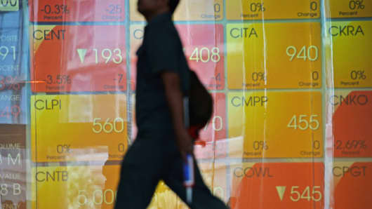 A man walks past an electronic board displaying share prices at the Indonesia Stock Exchange (IDX) in Jakarta, Indonesia, on Thursday, April 10, 2014.
