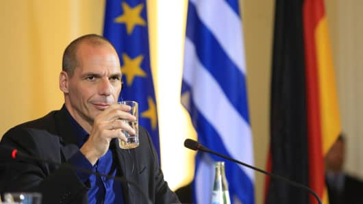 Yanis Varoufakis, Greece's finance minister, holds a glass of water during a news conference with Wolfgang Schaeuble, Germany's finance minister