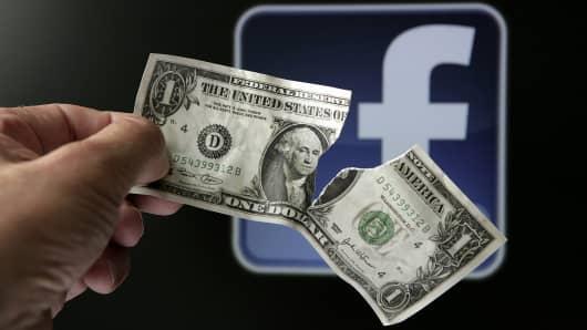 Torn dollar bill in front of Facebook logo
