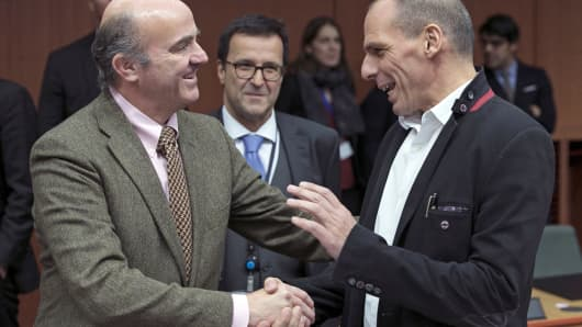 Spanish Finance Minister Luis de Guindos, left, talks with Greek Finance Minister Yanis Varoufakis at a euro zone finance ministers meeting to discuss Athens' plans to reverse austerity measures, in Brussels, Feb. 20, 2015.