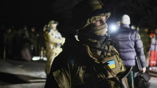 Ukrainian forces stand guard during a prisoner exchange on February 21, 2015 near Zholobok, Ukraine.