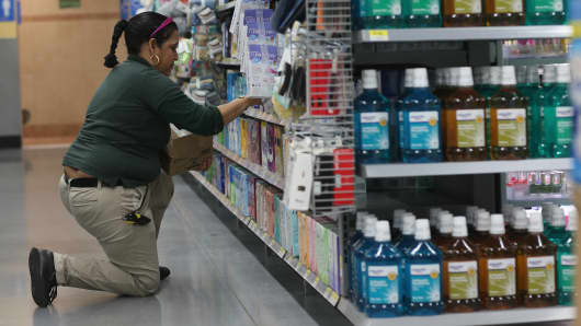 Employee Clara Martinez stocks the shelves at a Walmart store on Feb. 19, 2015, in Miami.