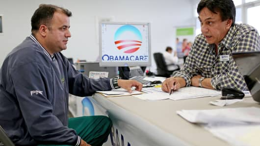 Ariel Fernandez, left, sits with Noel Nogues, an insurance advisor with UniVista Insurance, as he signs up for health insurance under the Affordable Care Act in Miami on Feb. 5, 2015.