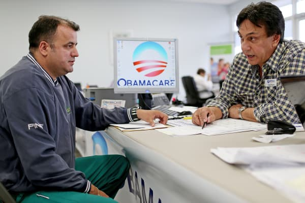 Ariel Fernandez, left, sits with Noel Nogues, an insurance advisor with UniVista Insurance, as he signs up for health insurance under the Affordable Care Act in Miami.
