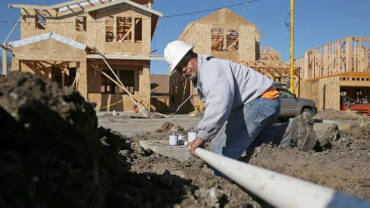 A worker prepares to move a piece of pipe into place as he works on new home construction in Petaluma, Calif.