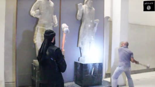 In this image made from video posted on a social media account affiliated with the Islamic State group on Thursday, Feb. 26, 2015, which has been verified and is consistent with other AP reporting, militants attack ancient artifacts with sledgehammers in the Ninevah Museum in Mosul, Iraq.
