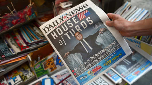 A woman buys a copy of the New York Daily News, featuring Speaker of the House John Boehner on the cover, following a government shutdown, Oct. 1, 2013, in New York.
