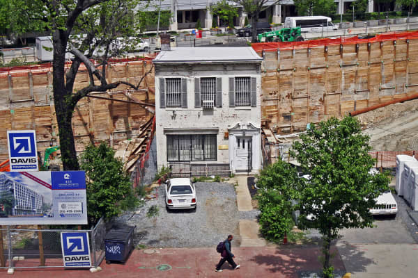 Austin Spriggs' row house on Massachusetts Ave., which he refused to sell to developers, is now an island surrounded by a huge hole in the ground.