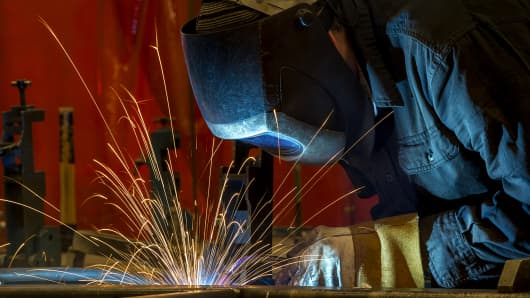 An employee welds the shell frame of a train car at the Siemens Industry manufacturing facility in Sacramento, California.