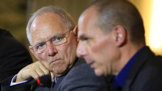 Wolfgang Schaeuble, Germany's finance minister, left, looks towards Yanis Varoufakis, Greece's finance minister.