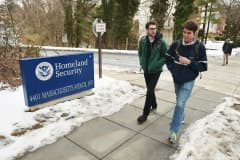 Pedestrians walk past a sign outside of a Department of Homeland Security complex on February 23, 2015 in Washington, DC.