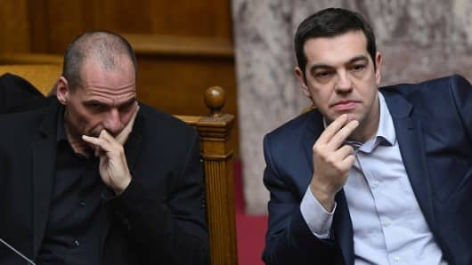 Greek Prime Minister Alexis Tsipras (R) sits next to Finance Minister Yianis Varoufakis.