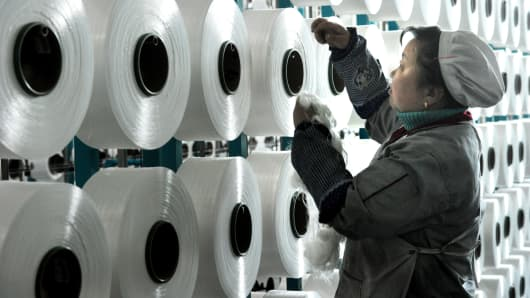 Chinese worker making blankets for export at a factory in Yiwu, Zhejiang, China.