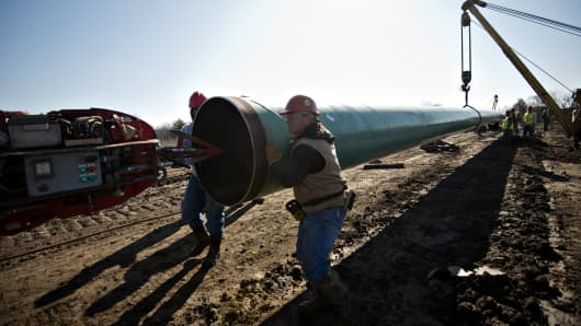 Workers move a section of pipe during construction of the Gulf Coast Project pipeline in Atoka, Oklahoma.