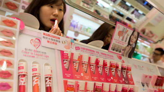 A customer tries out a lipstick at an Amorepacific Etude House store in Seoul, South Korea.