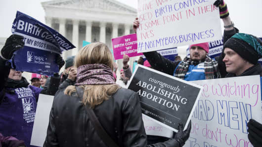 Activists with opposing views about contraceptive health care mix outside the Supreme Court March 25, 2014 in Washington, DC.