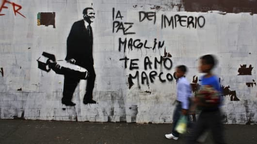 File photo: Children walk past anti-American graffiti in Caracas. President Obama announced new sanctions against seven Venezuelans on March 8, 2015.