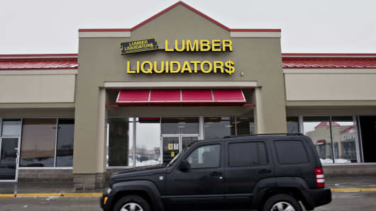 A car drives past a Lumber Liquidators Holdings Inc. store in Lombard, Illinois, U.S., on Tuesday, March 3, 2015.
