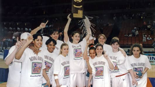 UConn star Rebecca Lobo, center, raises the NCAA trophy after winning the finals against the University of Tennessee, Minneapolis, MN, April 1995.