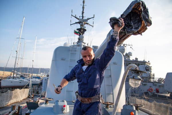 """An Italian sailor from the frigate """"Alieso"""" removes a cover from a cannon in the Black Sea port of Varna, Bulgaria, March 9, 2015."""
