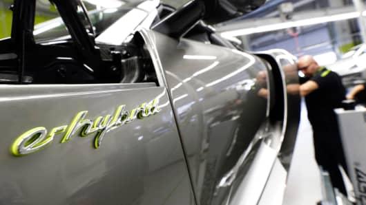 A worker assembles a new Porsche 918 Spyder e-hybrid sports car at the Porsche factory in Stuttgart-Zuffenhausen, Germany.
