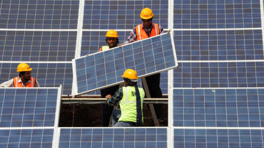 Indian workers install solar panels at the Gujarat solar park in Western India's Gujarat state.