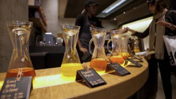 An employee helps a customer at a Teavana tea bar in New York.