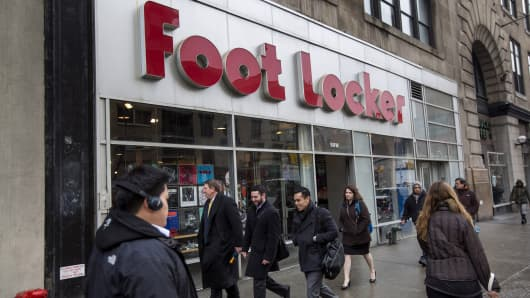 Pedestrians walk past a Foot Locker store in New York.