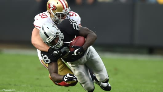 Latavius Murray #28 of the Oakland Raiders is tackled by Chris Borland #50 of the San Francisco 49ers in the second quarter at O.co Coliseum on December 7, 2014 in Oakland, California.