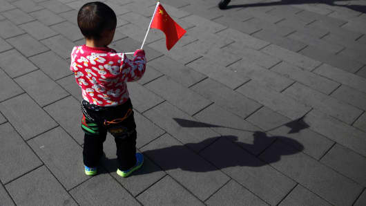 A child holds a Chinese national flag at Tiananmen Square in Beijing, China.