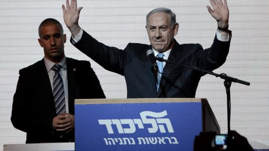 Benjamin Netanyahu greets supporters at the party's election headquarters after the first results of the Israeli general election on March 18, 2015