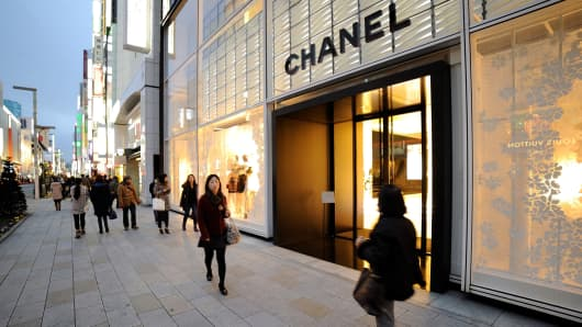 Shoppers walking past a Chanel store