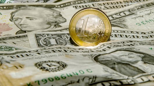 A one-euro coin is pictured on U.S. currency notes in Godewaersvelde, Northern France, March 13, 2015.