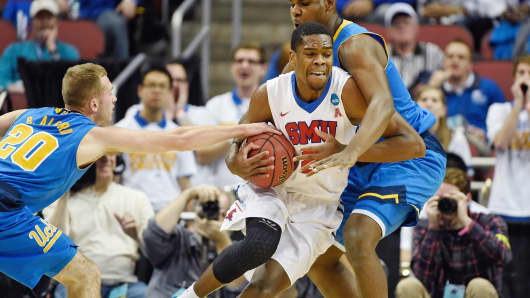 Southern Methodist University's Yanick Moreira (2) drives against UCLA's Tony Parker (23) and Bryce Alford (20) during the first half of an NCAA tournament second-round college basketball game in Louisville, Ky., March 19, 2015.