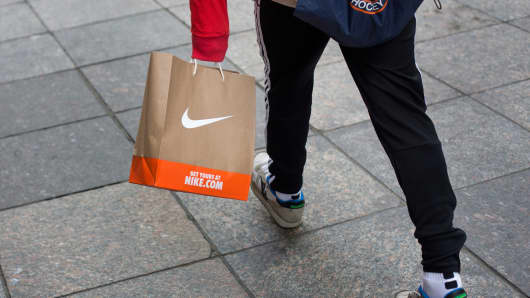 Shopper carrying a Nike shopping bag in New York.