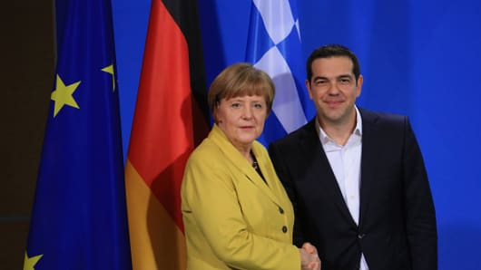 Angela Merkel, Germany's chancellor, left, stands for a photograph with Alexis Tsipras, Greece's prime minister.
