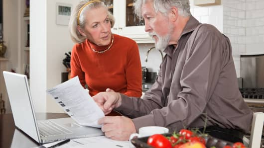 Senior couple looking concerned with paperwork and computer