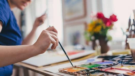Artist dabbing paint brush in palette