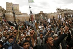 Shi'ite Muslim rebels hold up their weapons during a rally against air strikes in Sanaa March 26, 2015.