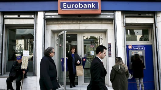 People are seen in front of a Eurobank branch in Athens, Greece, March 19, 2015.