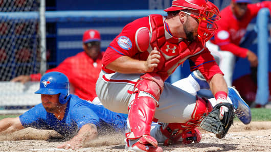 Toronto Blue Jays' Kevin Pillar dives safely into home past Philadelphia Phillies' catcher Cameron Rupp during the sixth inning of a spring training baseball game in Dunedin, Fla., March 31, 2015.