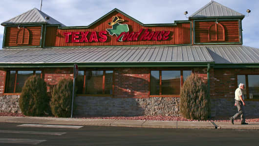 A man walks past a Texas Roadhouse restaurant in Arvada, Colo.