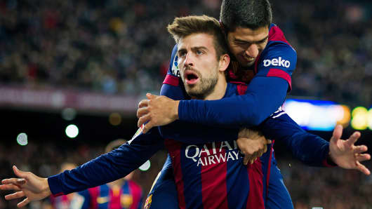 FC Barcelona's Gerard Pique, left, celebrates with teammate Luis Suarez after scoring his team's third goal during the La Liga match between FC Barcelona and RCD Espanyol in Barcelona, Spain.