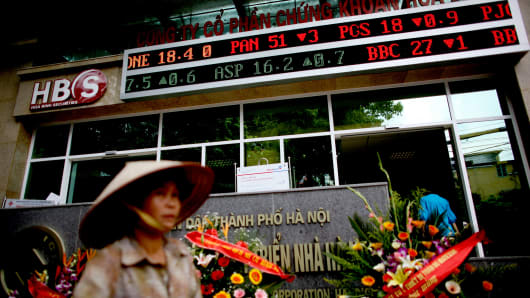 Stock prices are shown on a ticker outside a securities firm in Hanoi, Vietnam.