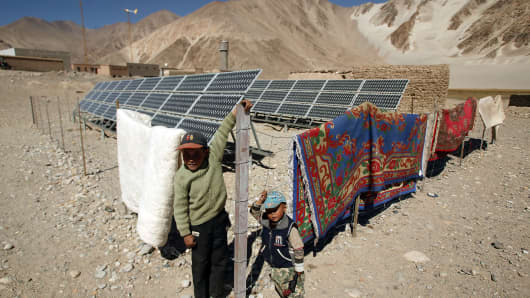 Two Uighur children play around the solar panels in the remote Bulunkou township in the mountains south of Kashgar, Xinjiang, China.