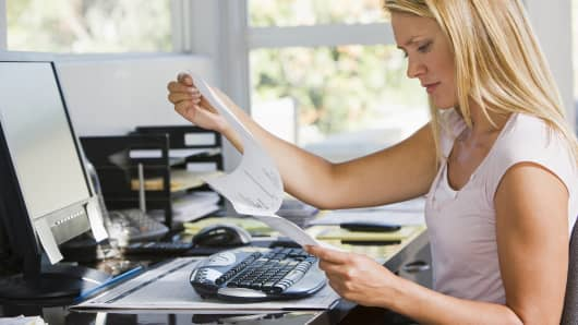 Woman looking at paperwork in home office