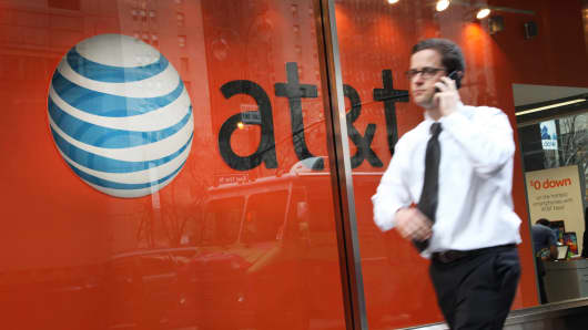 A pedestrian passes an AT&T store in New York.